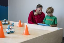 Photo of a man and boy with a robot controller