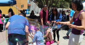 Photo of families making giant bubbles outdoors.