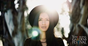 Headshot photo of a woman wearing a large-brimmed hat, sunlit from behind. Photo by Ursula Vari.