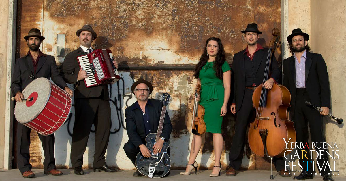 Photo of klezmer music group Kugelplex, with band members standing lined up holding their instruments in front of a worn industrial door