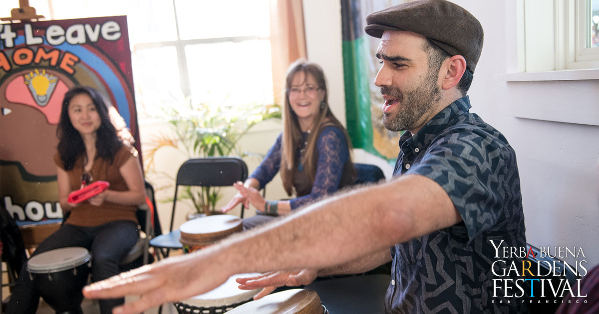 Aaron Kierbal on the right, facing the left, one arm outstretched in front, the other arm on top of a drum. Behind and the left of Aaron are two people, smiling and watching Aaron play, seated with drums between the knees.