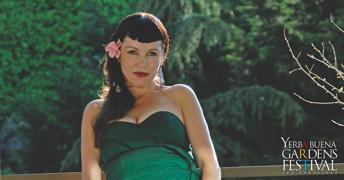 Lavay Smith leaning slightly back to the left, in front of greenery, wearing a pink flower on her ear, wearing a green strapless dress