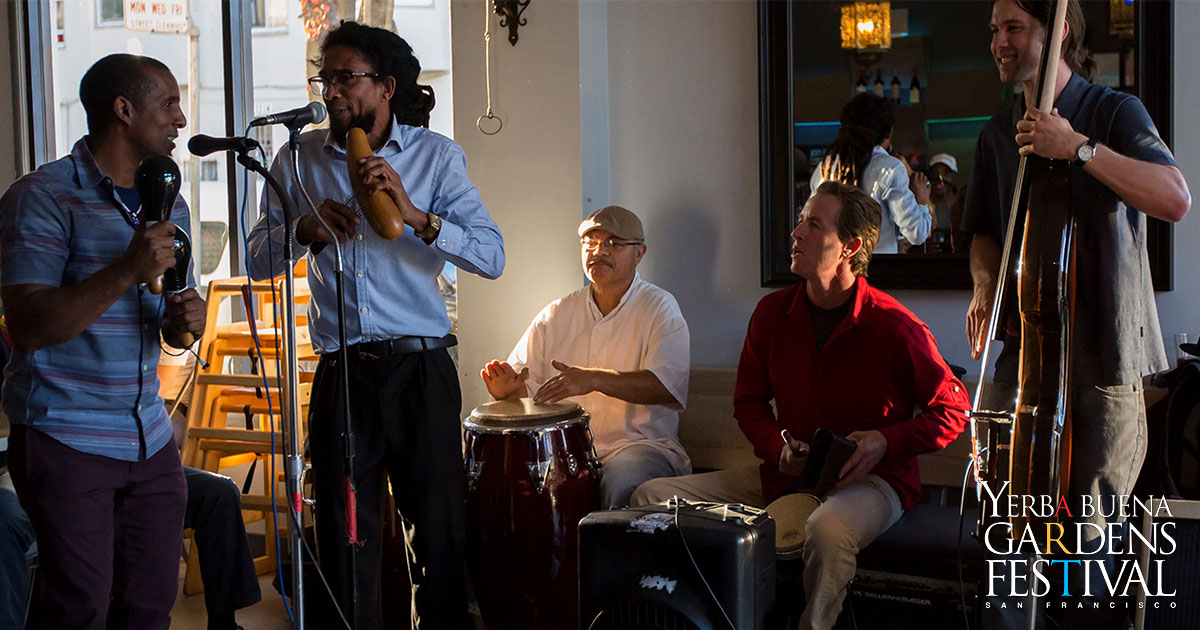 Band members of Sentimiento y Mañana in cafe, singing and playing music on various instruments.