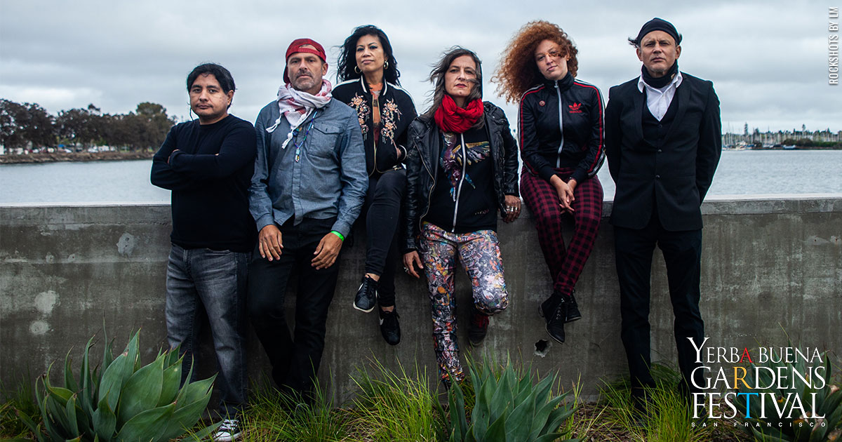 Six members of LoCura standing against a ledge, outside uncer overcast skies, with a body of water behind them.