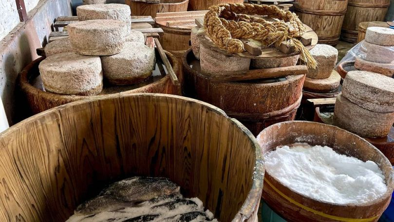 In Kitashina's storeroom, 30kg stones weigh down wooden tubs packed with salted, curing fish (Credit: Tom Schiller)