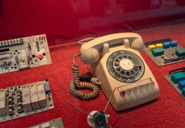 Vanhanaikainen kiekkopuhelin punaisen kankaan päällä, ympärillä elektroniikkaa