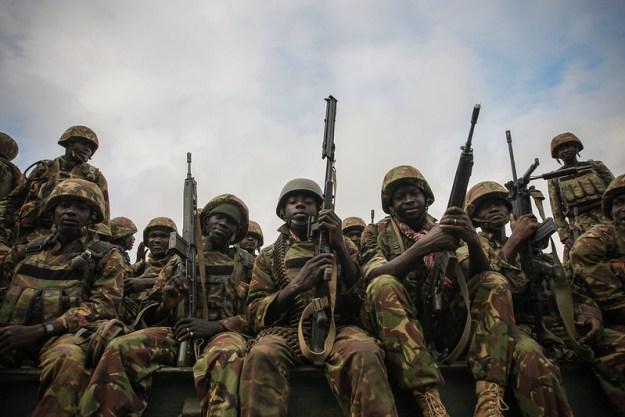 Maastopukuisia kenialaisia sotilaita istumassa rivissä rynnäkkökiväärejä pidellen