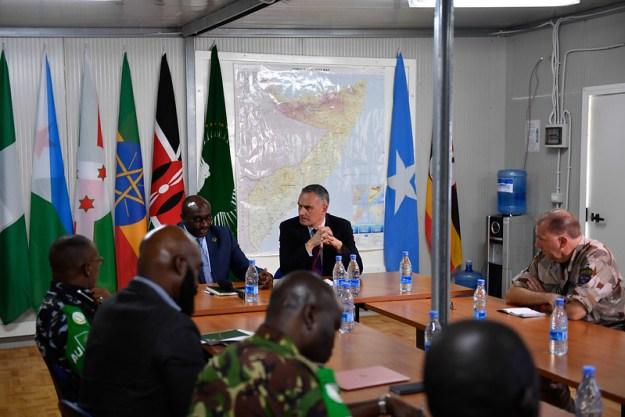 Miehiä maastokuvioisissa univormuissa ja puvuissa istumassa pöydän ympärillä, taustalla Somalian kartta ja Afrikan maiden lippuja