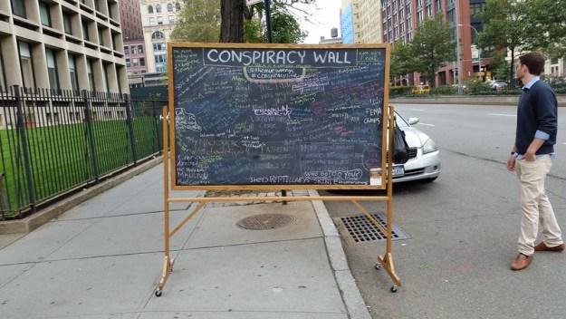 """Liitutaulu keskellä jalkakäytävää, yläotsikkona """"Conspiracy Wall"""" ja sen alla tiheään kirjoitettua tekstiä, taulun oikealla puolella siniseen neuleeseen ja kauluspaitaan pukeutunut mies katsoo muualle"""