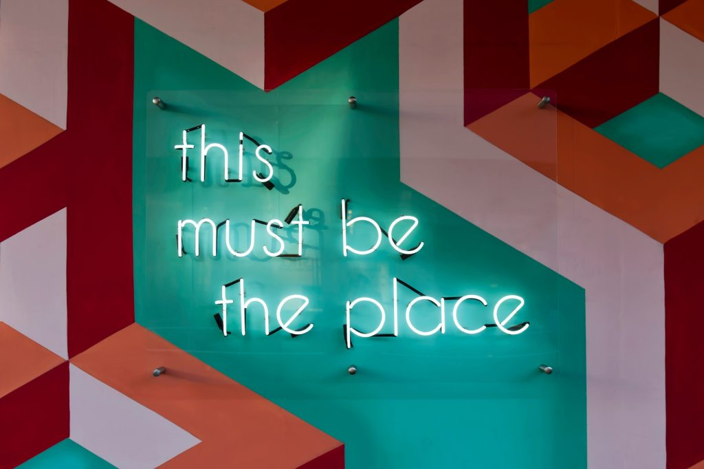 A neon sign reads 'this must be the place'