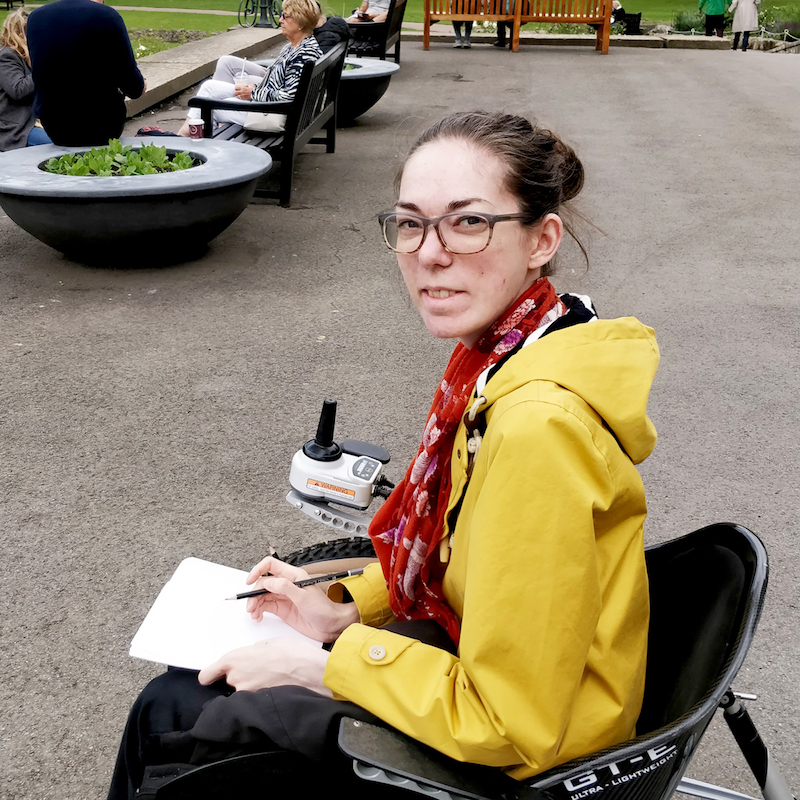 Elki in her favourite yellow coat, sitting in a wheelchair, drawing in a sketchbook