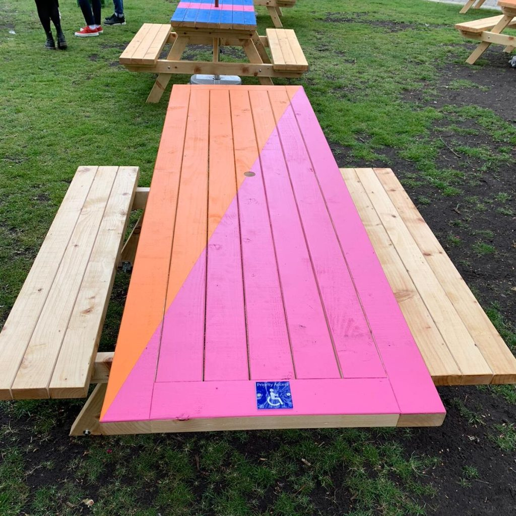 A wooden picnic table with fixed benches on either side. One end of the tabletop projects towards the camera and has a 'wheelchair symbol' on it