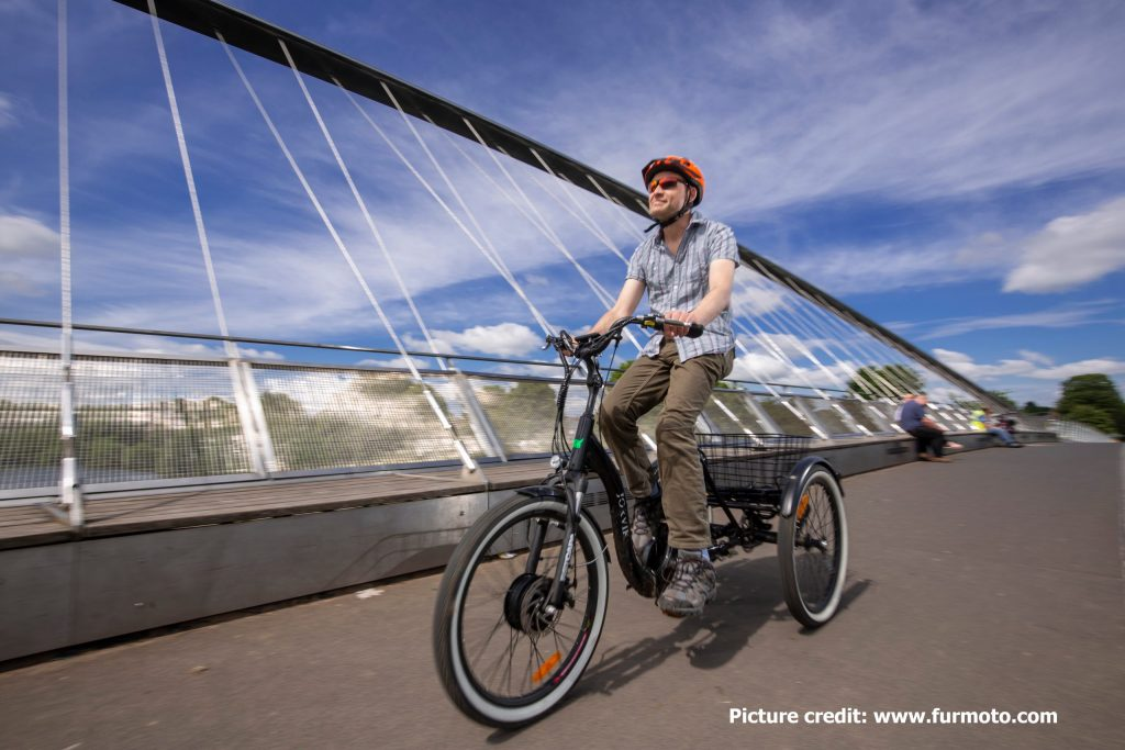A person on a trike is crossing Millenium Bridge