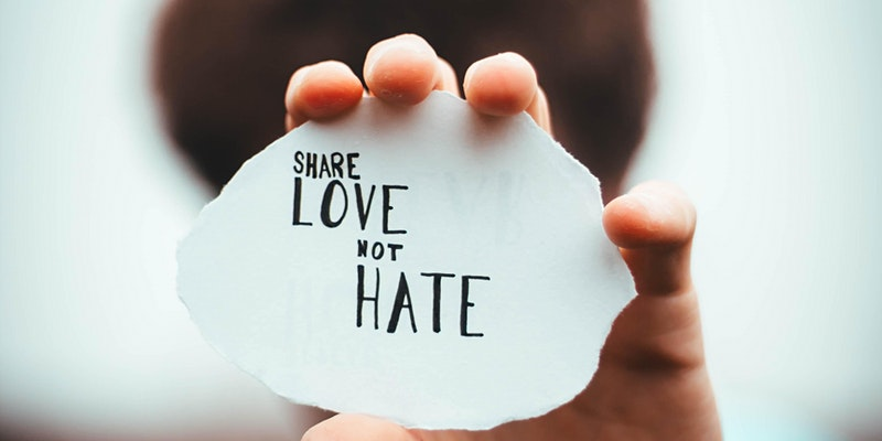 Hand holding a fragment of paper out in front of them that reads Share Love Not Hate