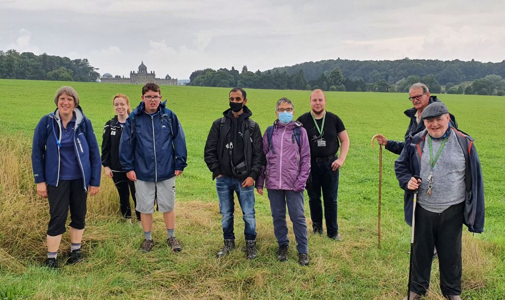 Group of walkers in a green field with a stately home in the distance