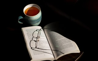 Cup of tea, a book and a pair of glasses