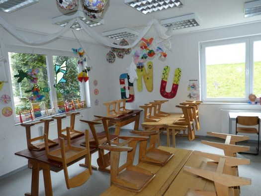 Image: Children's classroom, wooden chairs on wooden tables with bunting and pictures on walls and roof