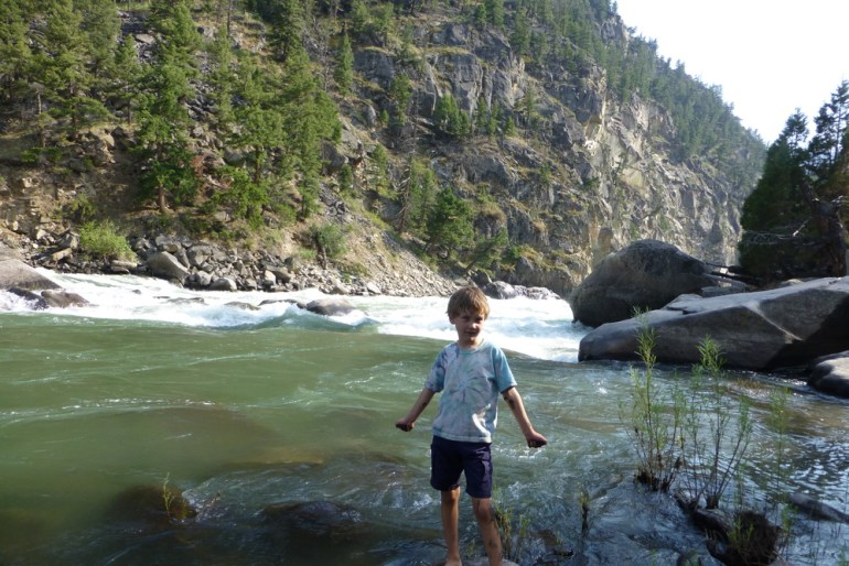 Boy near rapids in yellowstone