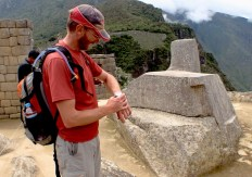 B. checking his watch against the Inca's sun dial (that may or may not have been a sun dial)