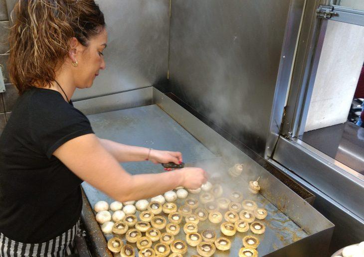 Chica preparando los champiñones en el Bar Angel