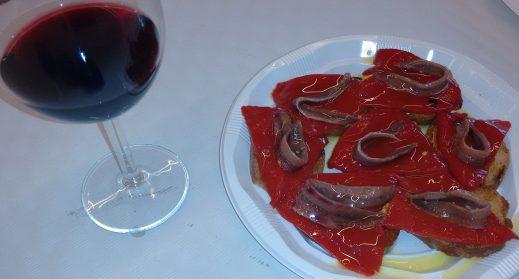 Tosta de pimiento rojo y anchoa con aceite y Copa de vino tinto