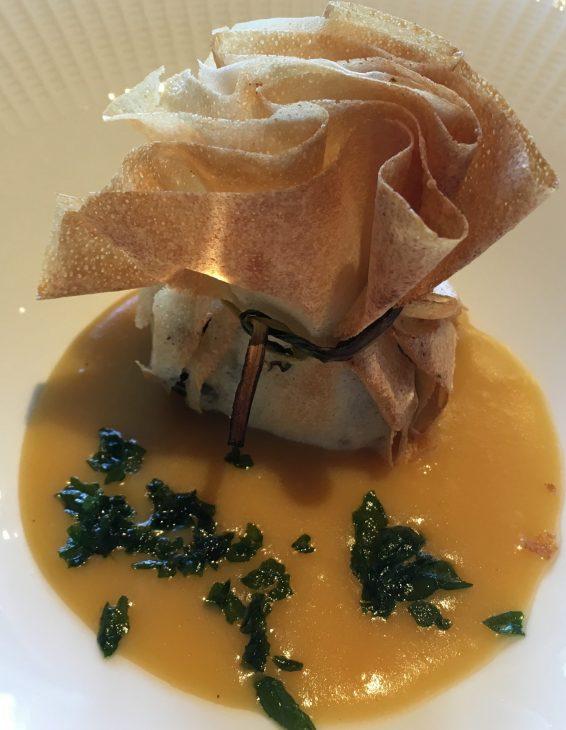 Bolsita de queso de cabra, espinaca fresca, pasas y nueces, con crema de calabaza y naranja