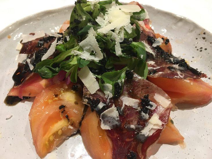 Ensalada de tomate pelado a mano, cecina seleccionada, cebolla roja encurtida y unas lascas de queso parmesano