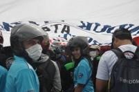 Peserta demo buruh berlindung dari sinar matahari.