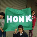 """A photo of children in Salinas, CA holding a green banner reading """"Honk"""". Part of the Honk for Peace rally, May 2014."""