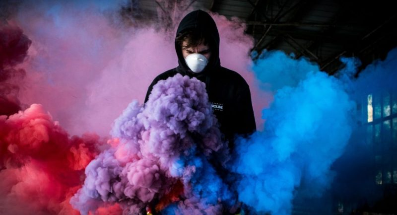 Man in black hoody wearing face mask making smoke art to illustrate Coronavirus COVID-19 and what brands can do about their drinks marketing right now