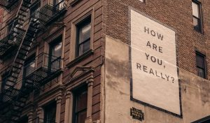 alcohol and mental health image shows street art paste up poster in new york reading How Are You Really?
