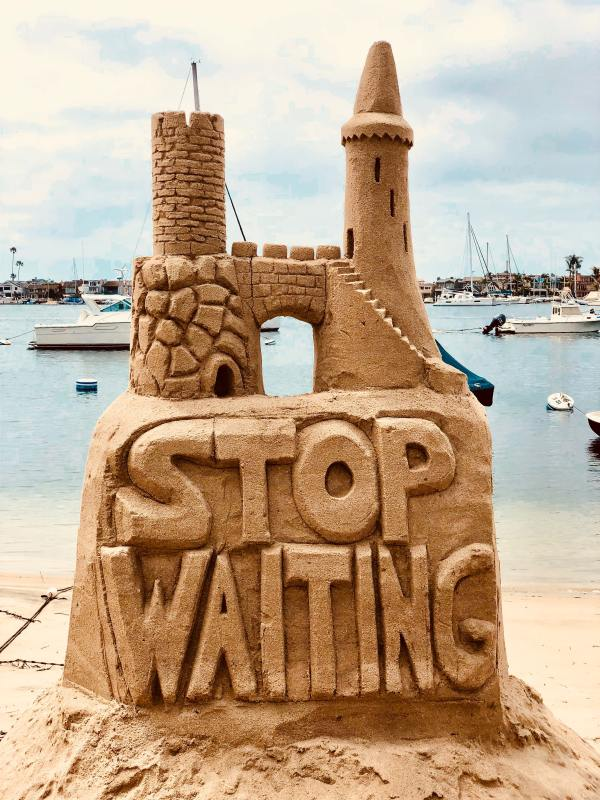 Why do we procrastinate and how to stop it depicted by words Stop Waiting carved on a castle of sand