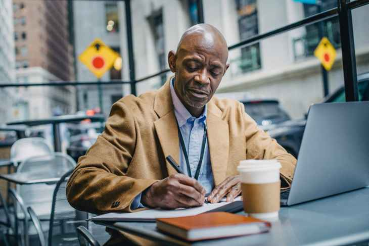 black male office worker writing on paper near laptop indoors