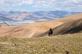 キャマユリ・ラを馬で駆け上がる遊牧民の青年