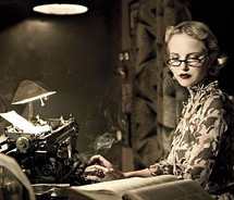 Woman typing on an old typewriter retro smoking
