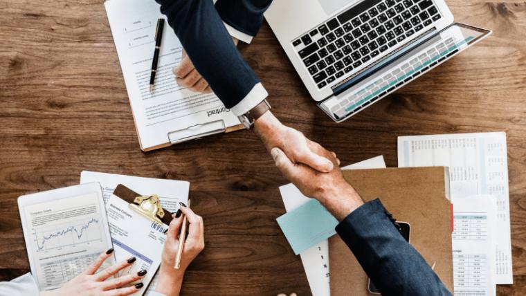 机の上で握手するビジネスマン男性たち