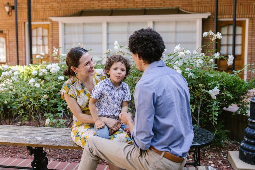 A smiling family sits outside enjoying their home recently remodeled by a Houston home exterior construction contractor.