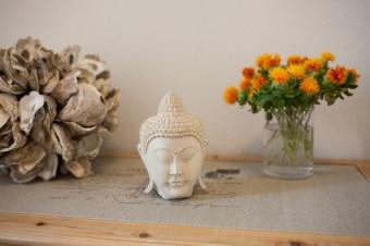 Detail eines geschnitzten Buddhakopfs mit Blumen auf der Anrichte - (c) yoga privé
