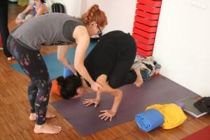 Teilnehmerinnen der Yogalehrer Ausbildung in Berlin bei Yoga & Cure. Die Leitung dieser Yoga Ausbildung obliegt Dr. med. Wiebke Mohme. Dr. Mohme ist Fachärztin & Ärztin für Ayurveda. Feli und Melanie üben hier Assists für die Krähe. Denn die Krähe ist ein beliebtes Yoga Asana. Balance wird sowohl in der Krähe, als auch in etlichen anderen Asanas geübt. Dein gesamtes Körpergefühl profitiert davon.