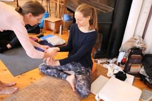 Dir ist beim Yoga sowohl Yogatradition als auch modernes Yoga wichtig? Dann bist Du in der Yoga Ausbildung bei Dr. Mohme genau richtig. Hier lernst Du ein medizinisch korrektes Yoga. Außerdem bereitet es Freude in dieser sehr angenehmen Yogaausbildungsgruppe dabei zu sein. Bereichere Dein Yoga, gehe noch tiefer & komme in die Yogalehrer Ausbildung mit Dr. med. Wiebke Mohme. Du lernst hier Wichtiges fürs Leben - weit über den Yoga hinaus! Auf diesem Bild siehst Du, wie Dr. Mohme einer Ausbildungsteilnehmerin eine besondere Unterstützung für die Handhaltung zeigt.