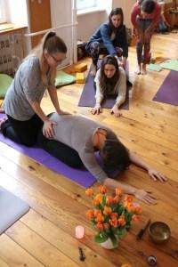 """Im Rahmen der Yogalehrer Ausbildung werden auch Assists geübt. Manche Yogis & Yoginis benutzen die Wörter """"hands on"""" oder """"Adjustments"""". Diese Englischen Worte sind zwar zu verstehen, jedoch insbesondere der zweite Begriff trifft nicht das Verständnis von Dr. Mohme. Denn es geht nicht darum jemanden zu richten, zu korrigieren oder gar abzuwerten, sondern im Positiven zu unterstützen. Und genau dies erlernst Du während des Yoga mit Dr. med. Wiebke Mohme. Hier siehst Du eine Ausbildungsteilnehmerin beim Üben von Assists. Sie unterstützt also die Yogaschülerin."""