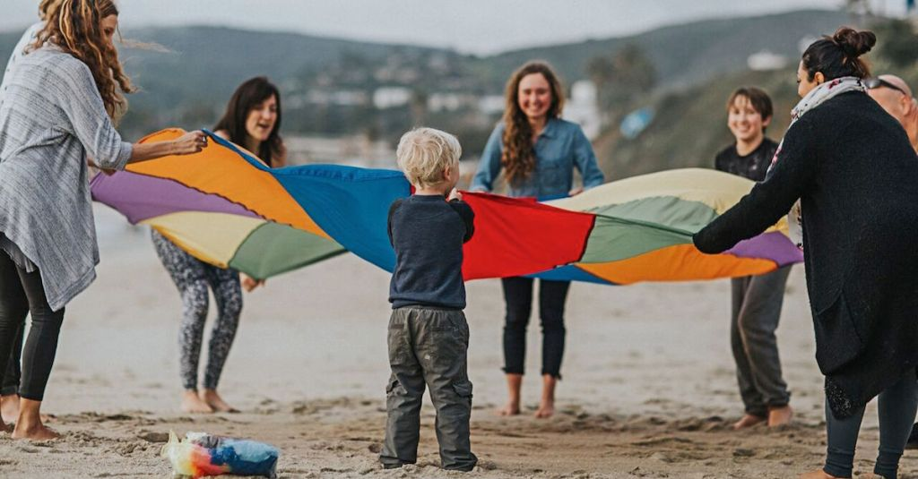 Trainees and Child Playing with a Parachute on the Beach