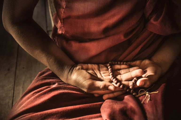 Monk doing yoga mudra while meditating