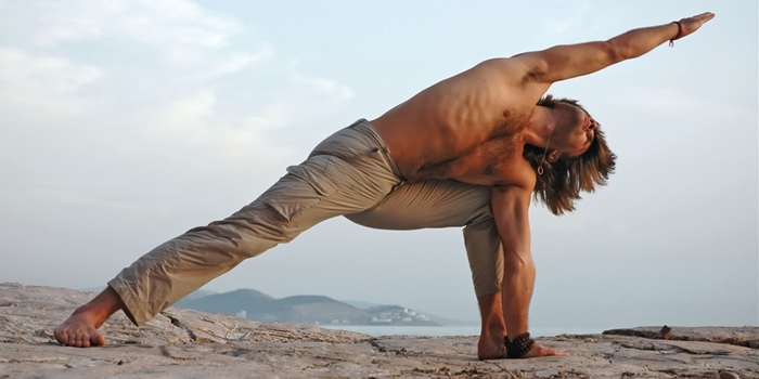 Man doing yoga outdoors. Parshvakonasana. Side view.