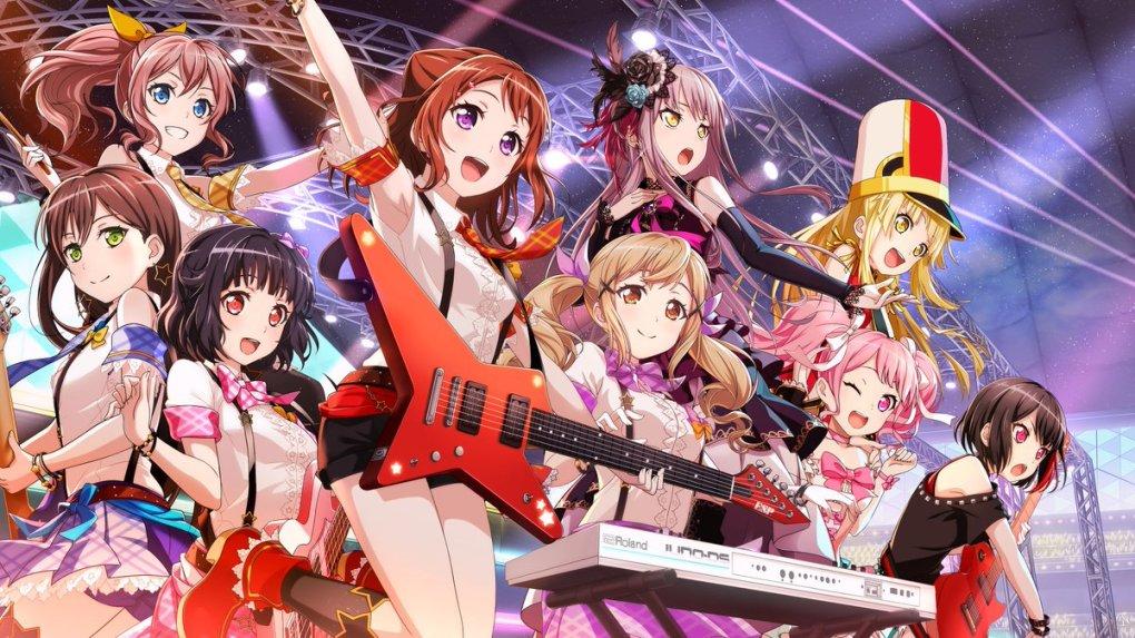 9 garotas com instrumentos musicais olhando da esquerda para a direita.