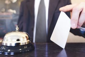 Reception service bell and receptionist holding a room key card.