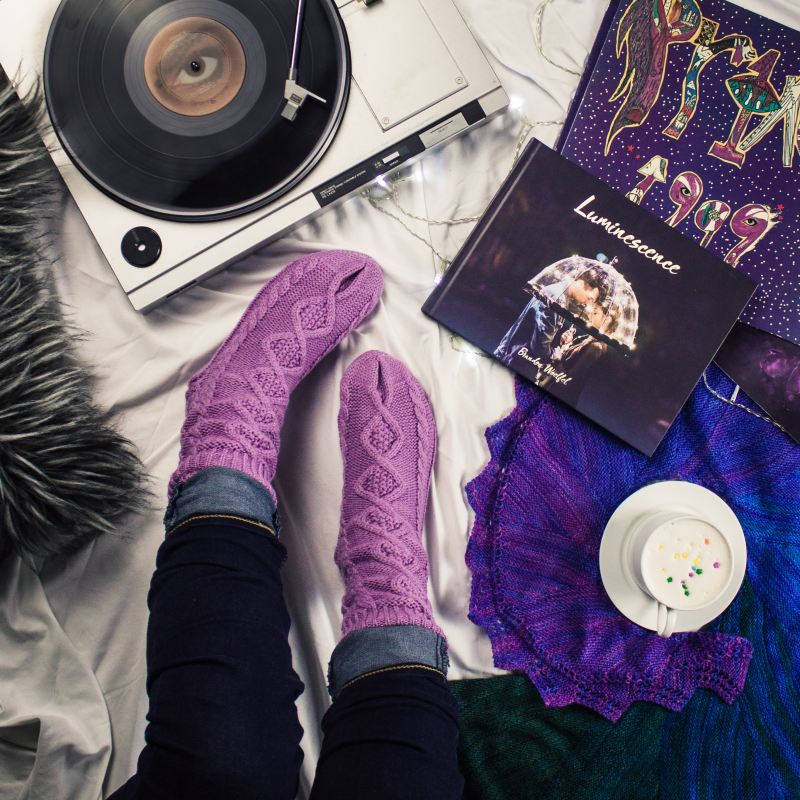 """A person sits on their bed, surrounded by their self care kit: a grey fuzzy pillow, purple knitted socks, a record player playing music, the photography book """"Luminescence"""" by Brandon Woelfel, a colorful print of """"Prince 1999,"""" hot chocolate with whipped cream and sprinkles, and a deep blue and purple knitted scarf."""