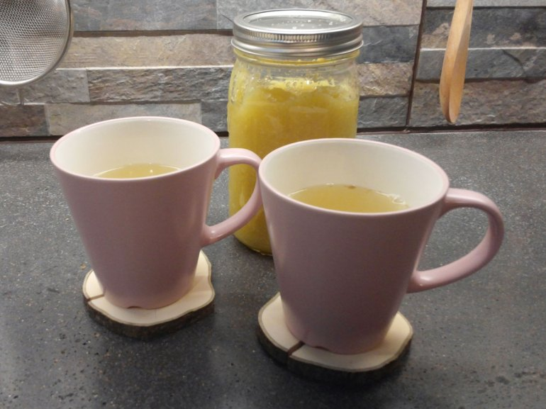 Two pink cups of ginger tea, a yellowish, slightly cloudy liquid. A mason jar full of the concentrated, yellowish ginger-sugar mixture is behind the cups.