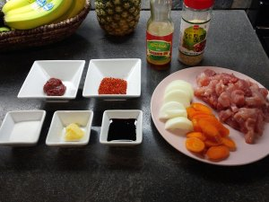 Ingredients are laid out in small square bowls and on a dish. In the square bowls on the left: hot pepper paste, hot pepper flakes, sugar, minced garlic, soy sauce. In bottles above: sesame oil, sesame seeds. On a ceramic plate on the right: chopped onions, chopped carrots, chopped pork.
