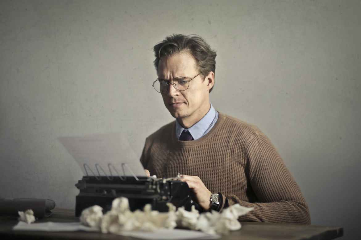 adult frowned male writer working on typewriter at home